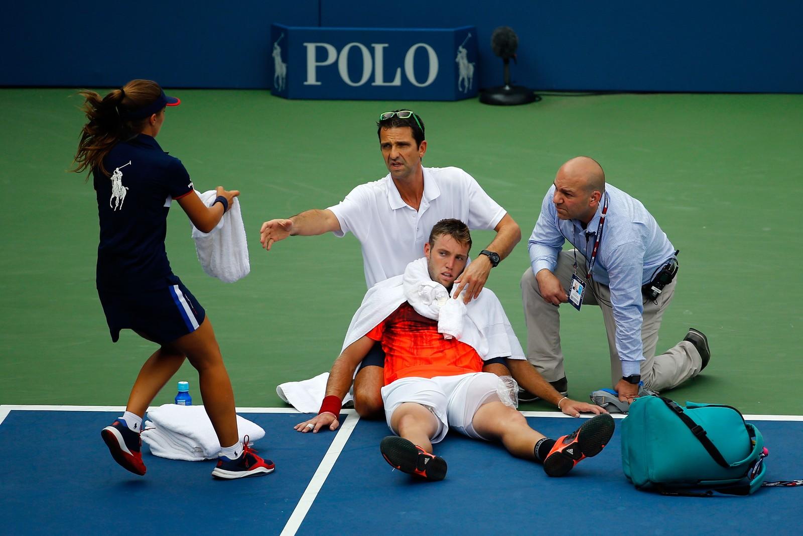 Amerikanske Jack Sock får hjelp etter at varmen fikk ham til å kollapse under en kamp i US Open. Sock ledet 2-1 i sett mot belgieren Ruben Bemelmans, da han fikk krampe og måtte hjelpes av banen.