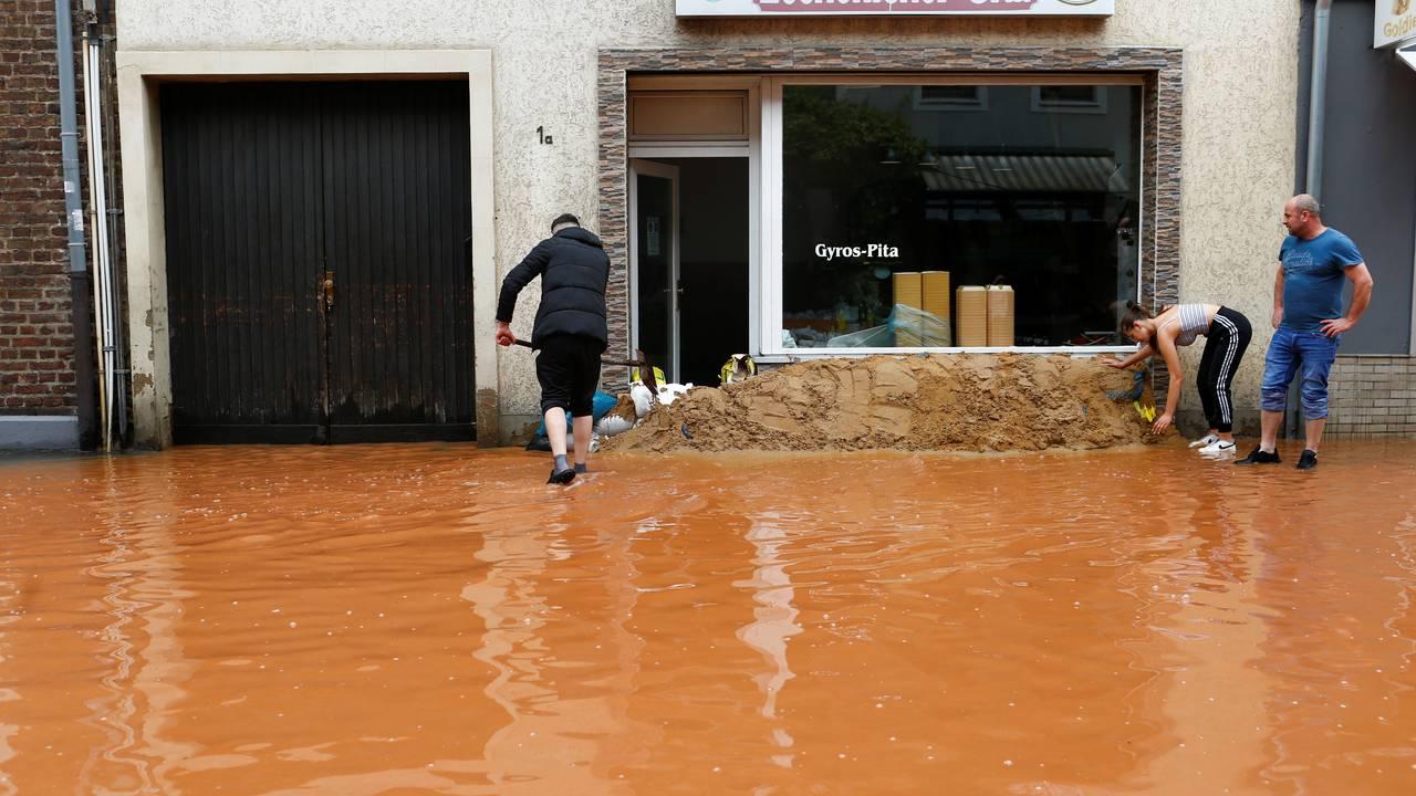 Gatene er blitt til elver og butikkeierne forsøker å redde arbeidsplassene sine.