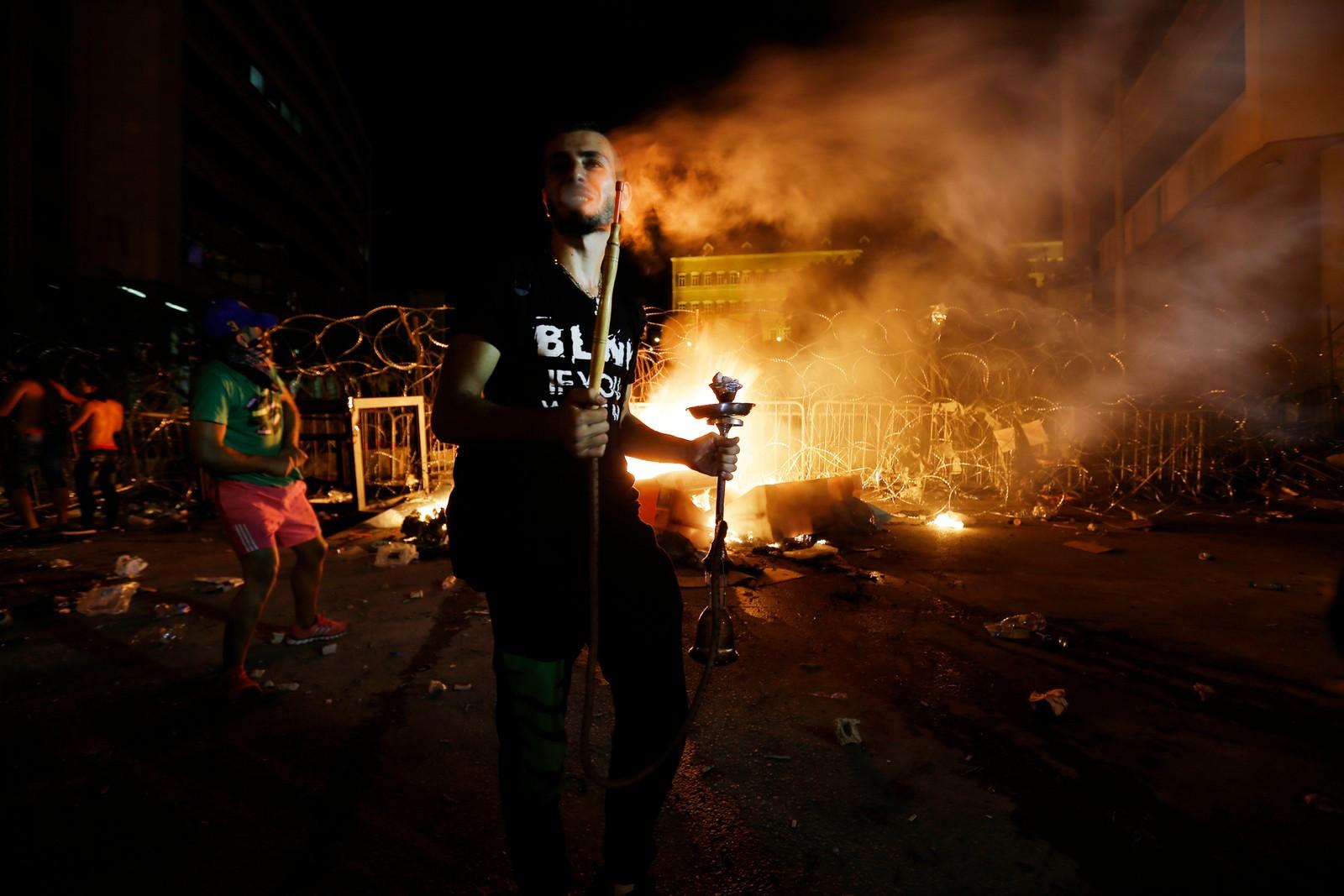 En av demonstrantene røyka vannpipe foran et påtent søppelberg. Demonstrasjonene utvikla seg etterhvert i voldelig retning, og politiet ble tilkalt.