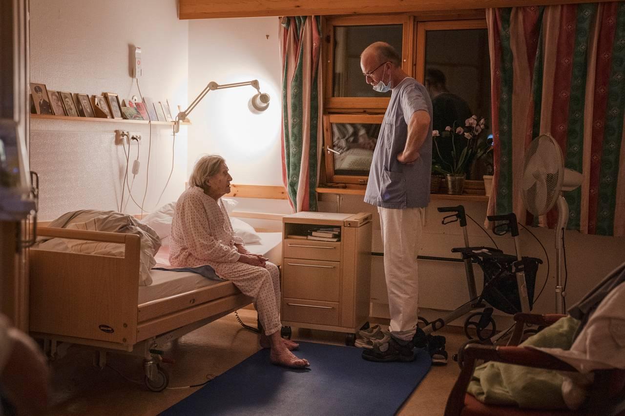 Eugenia sitter i sengen og møter blikket til nattevakten som står og ser litt bestemt på henne fra midt i rommet.