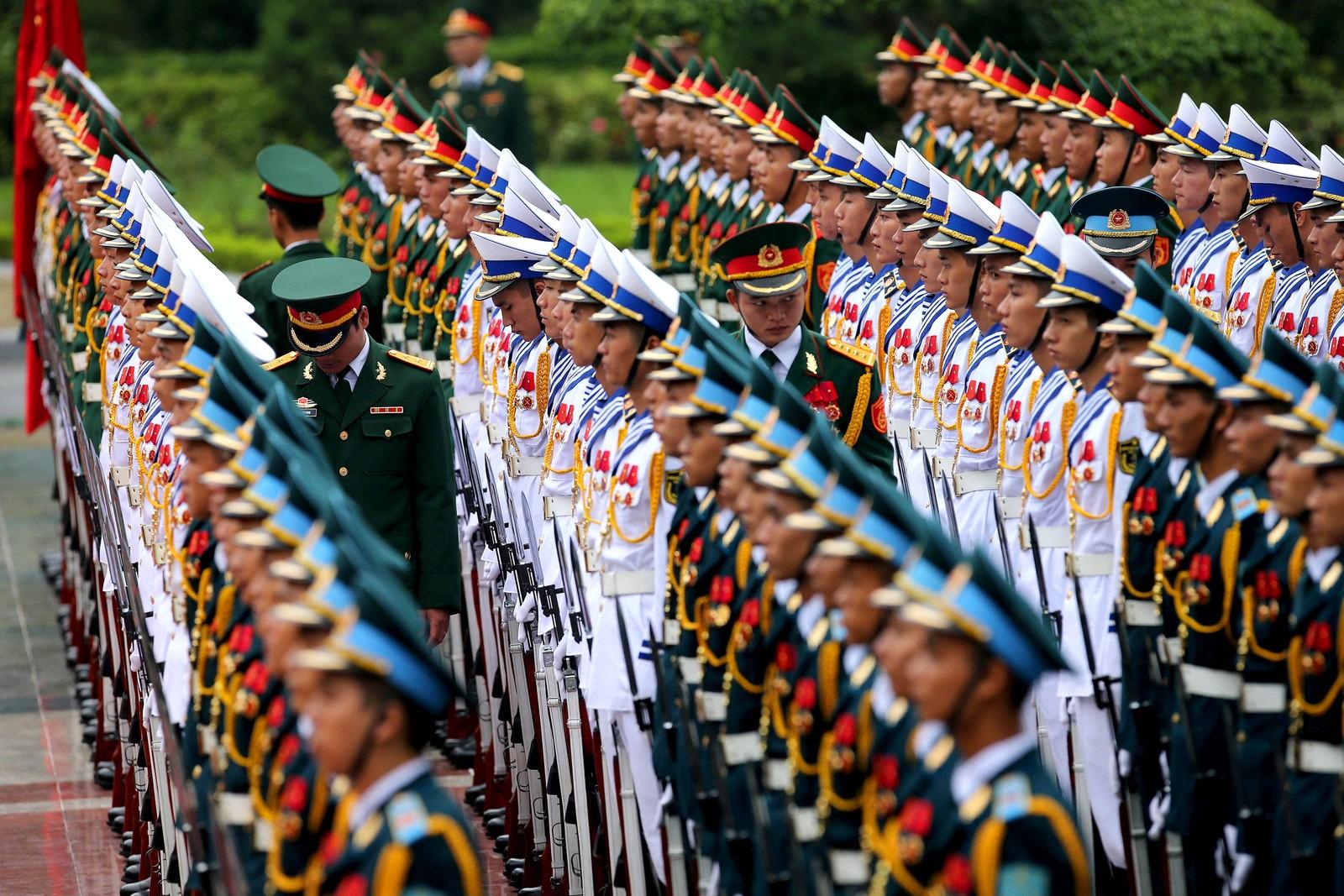Nesten alle helt rett på en linje. Soldater står æresvakt i Hanoi i Vietnam den 5. september. Frankrikes president Francois Hollande er på besøk i landet i to dager.