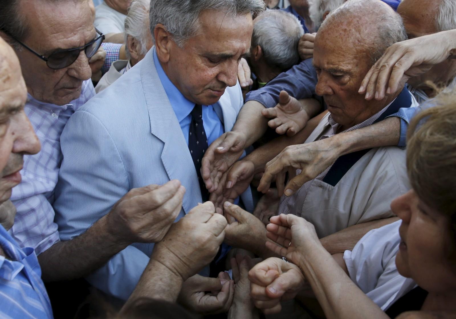 En bankansatt deler ut kølapper utenfor en bank i Aten mens greske pensjonister strekker armene fram for å få fatt i lappene.