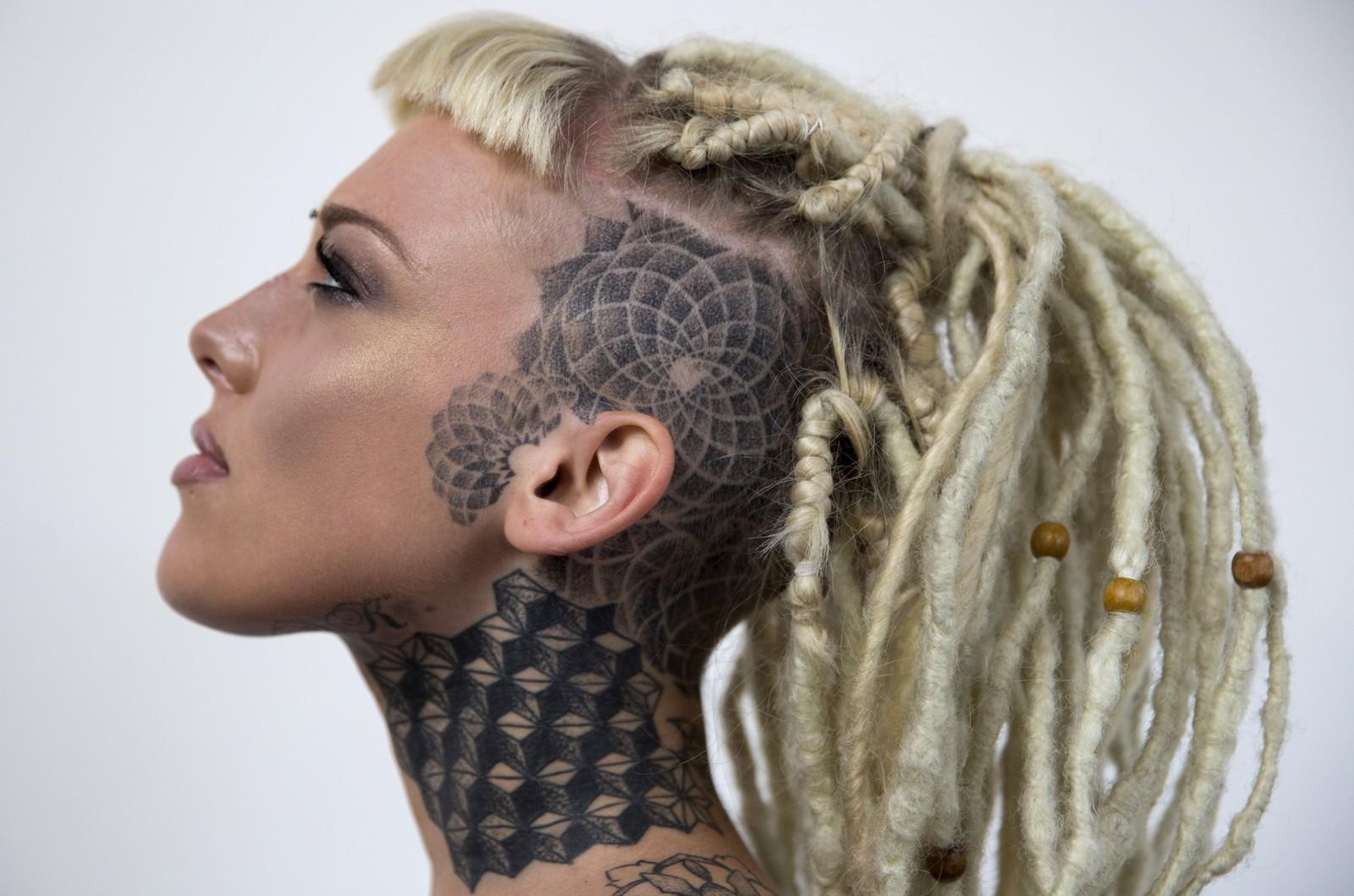 Lauren Brock viser seg fram for fotografene under den internasjonale tatoveringsmessa i London.