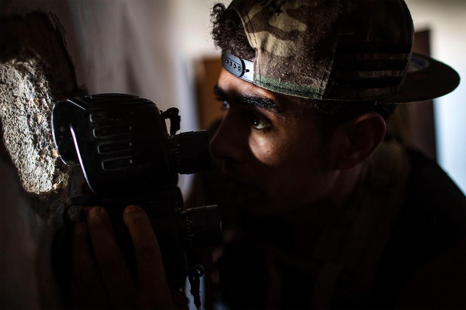 På utkikk etter fienden. En libysk soldat forsøker å få øye på IS-soldater under kamper i Sirte i Libya den 22. september.