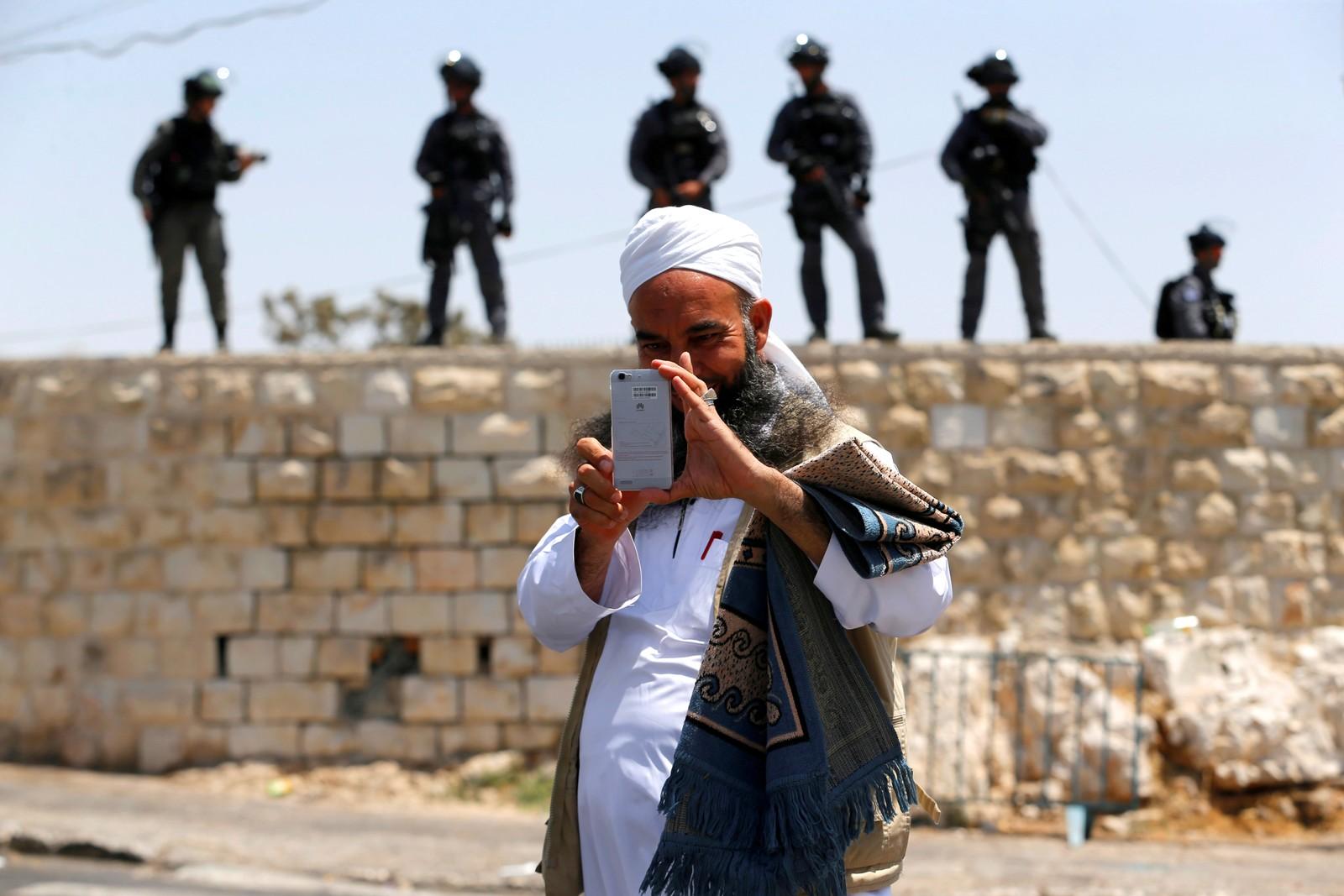 En palestinsk mann, en mobil og israelske grensevakter utenfor Jerusalem.