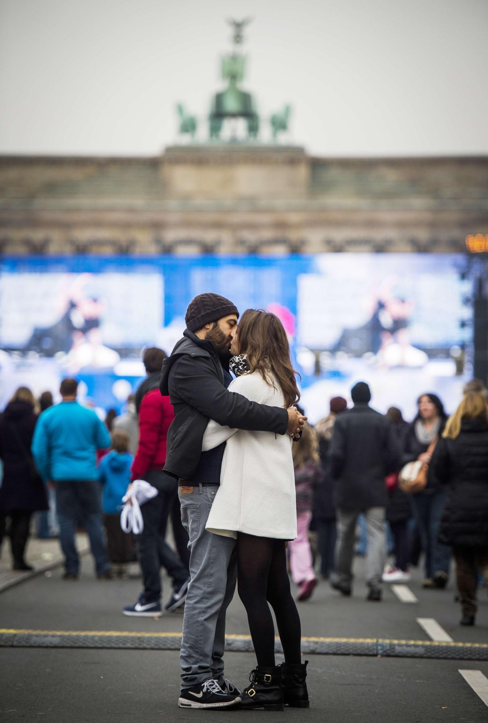 Et kyssende par foran Brandenburger Tor.