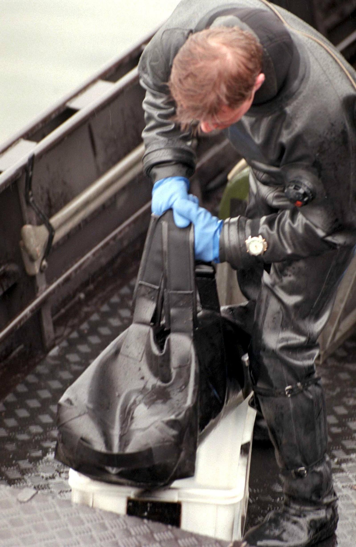 En svensk polititjenestemann undersøker en bag funnet i en kanal i sentrale Stockholm i forbindelse med Palme-etterforskningen. Inne i baggen fant de et skytevåpen.