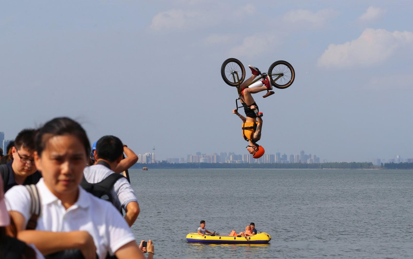 """En akrobatisk syklist på vei ut i det våte element under den årlige """"kast-deg-i-elva""""-arrangementet i Wuhan, Kina."""