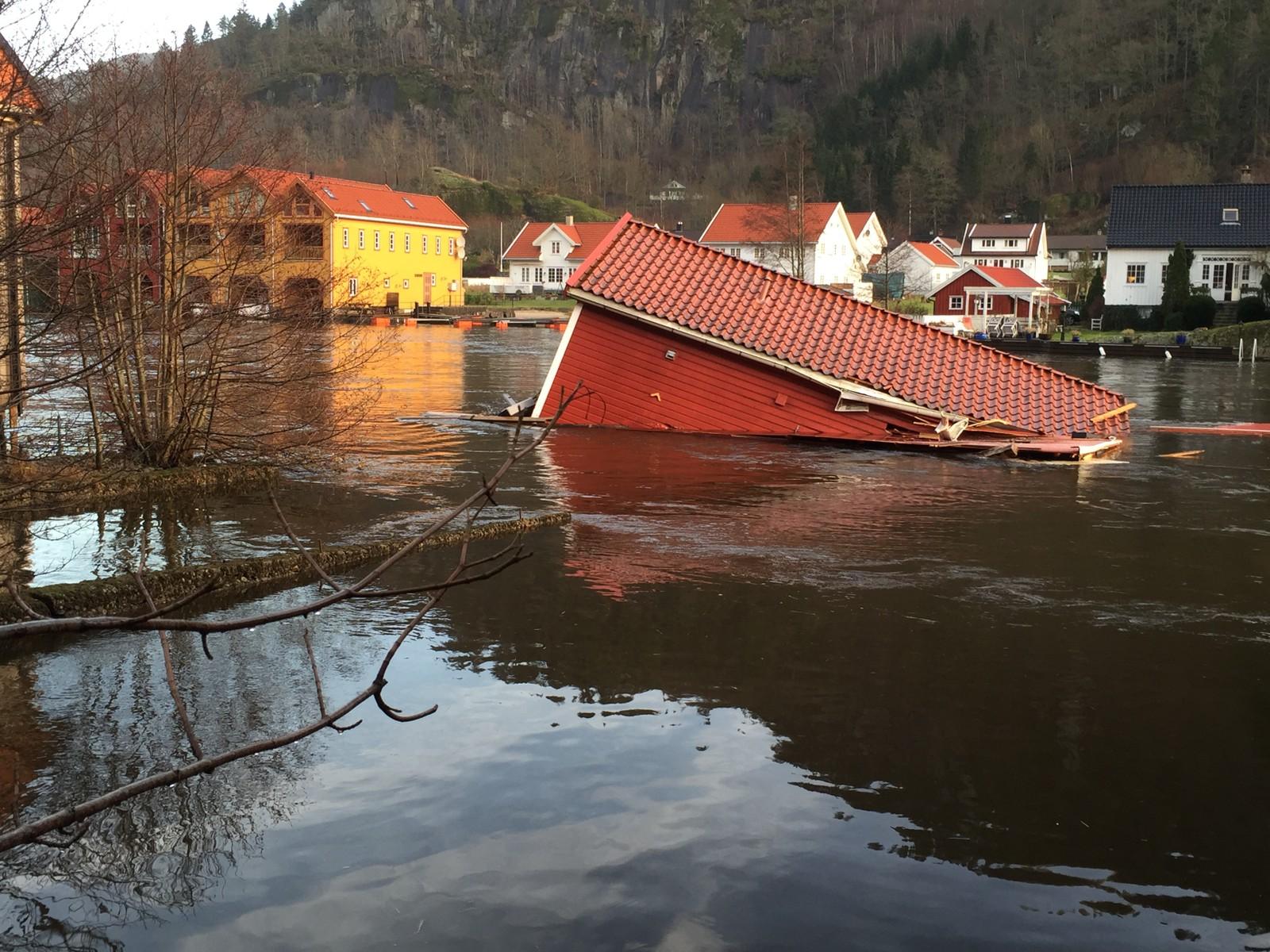 Et båthus i drift nedover Fedaelva mandag morgen. Vannstanden har gått ned, men mange hus og sjøboder er utgravd ved grunnmuren og står i fare for å rase ut i elva.