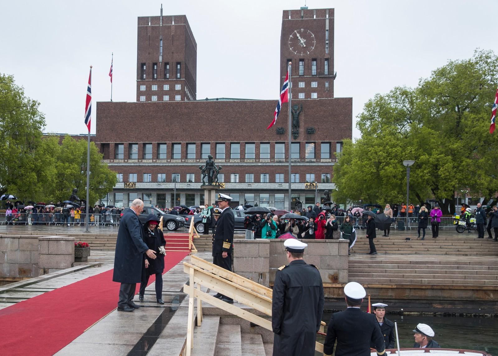 Publikum og et stort pressekorps utenfor rådhuset idet kong Harald og dronning Sonja ankommer Honnørbrygga for avreise til Kongeskipet Norge onsdag, der
