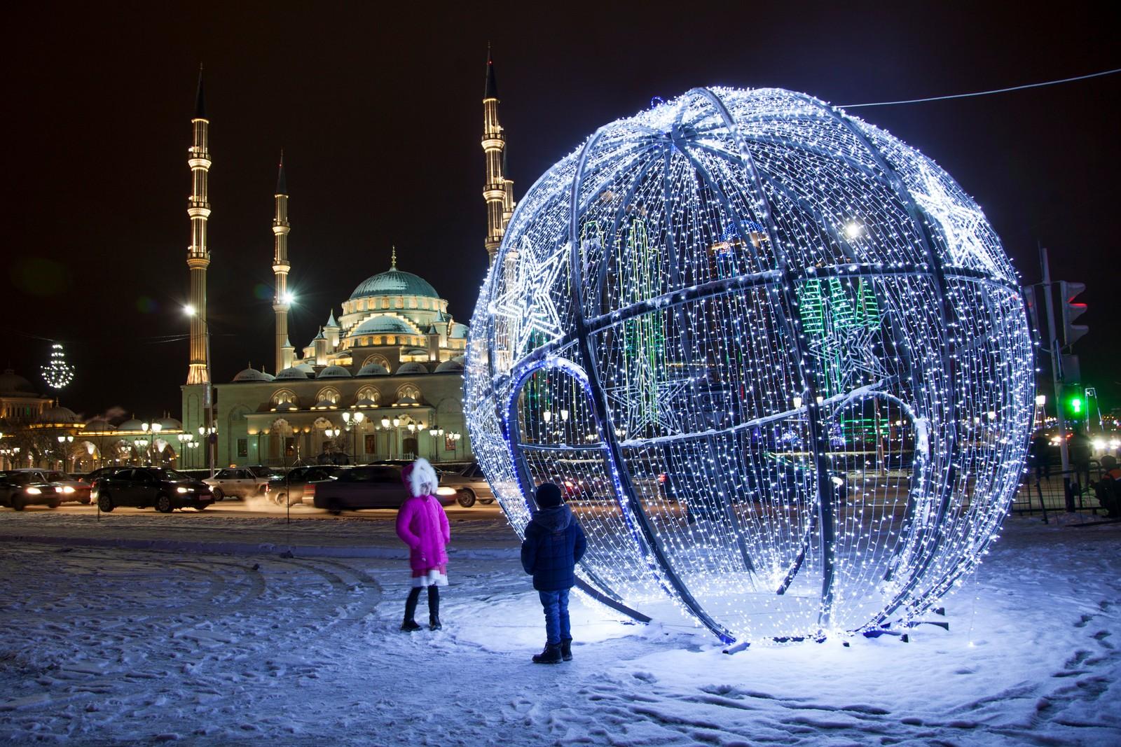 Barn ved juledekorasjoner utenfor en moske i Grozny i den russiske republikken Tsjetsjenia.