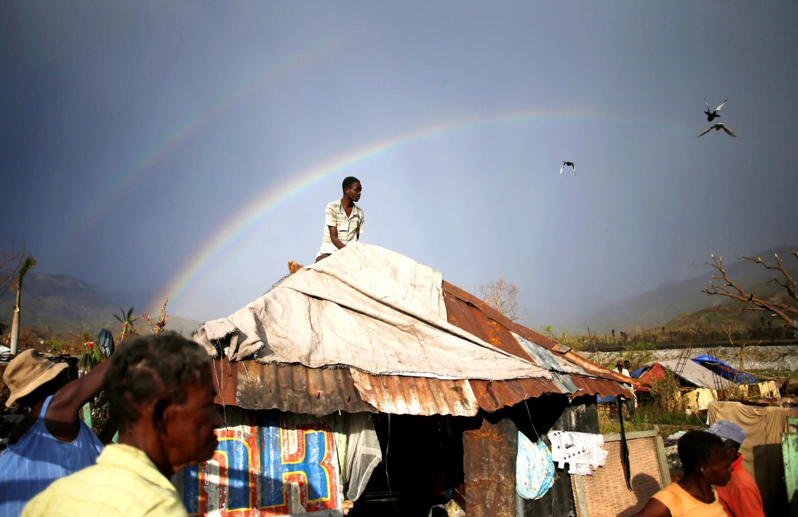 En mann forsøker å dekke huset sitt med presenning i et område av Haiti som opplevde orkanen Matthews ødeleggende krefter.