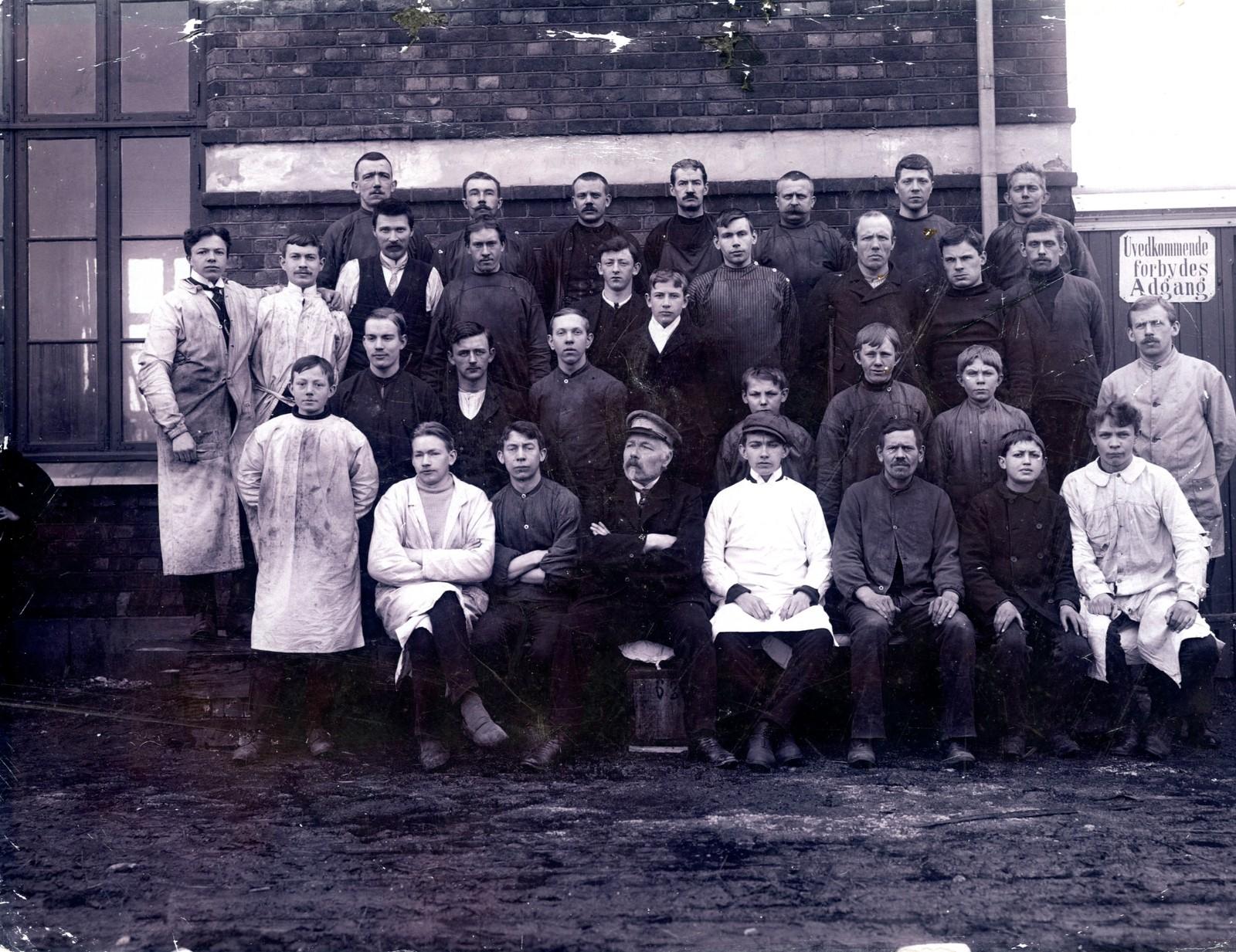 Ansatte ved Th. Marthinsen Sølvvarefabrikk A/S i arbeidsantrekk fotografert foran fabrikken, april 1910. Th. Marthinsen i midten.