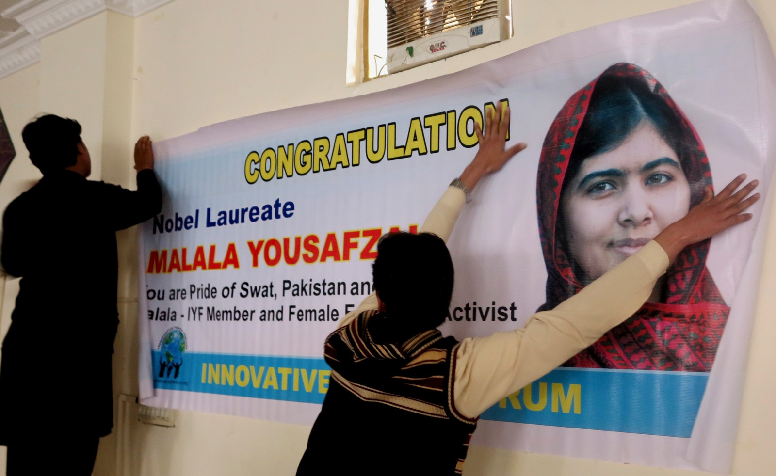 GRATULERER, MALALA: Students of Mingora, Pakistan, a hometown of Nobel Peace Prize laureate Malala Yousafzai, put a banner of her on a wall at a local school, Wednesday, Dec. 10, 2014. Malala's struggle for girls to be educated in a deeply conservative society led to a shooting against her by the Taliban two years ago. Malala and Kailash Satyarthi of India have received the Nobel Peace Prize for risking their lives to fight for children's rights.