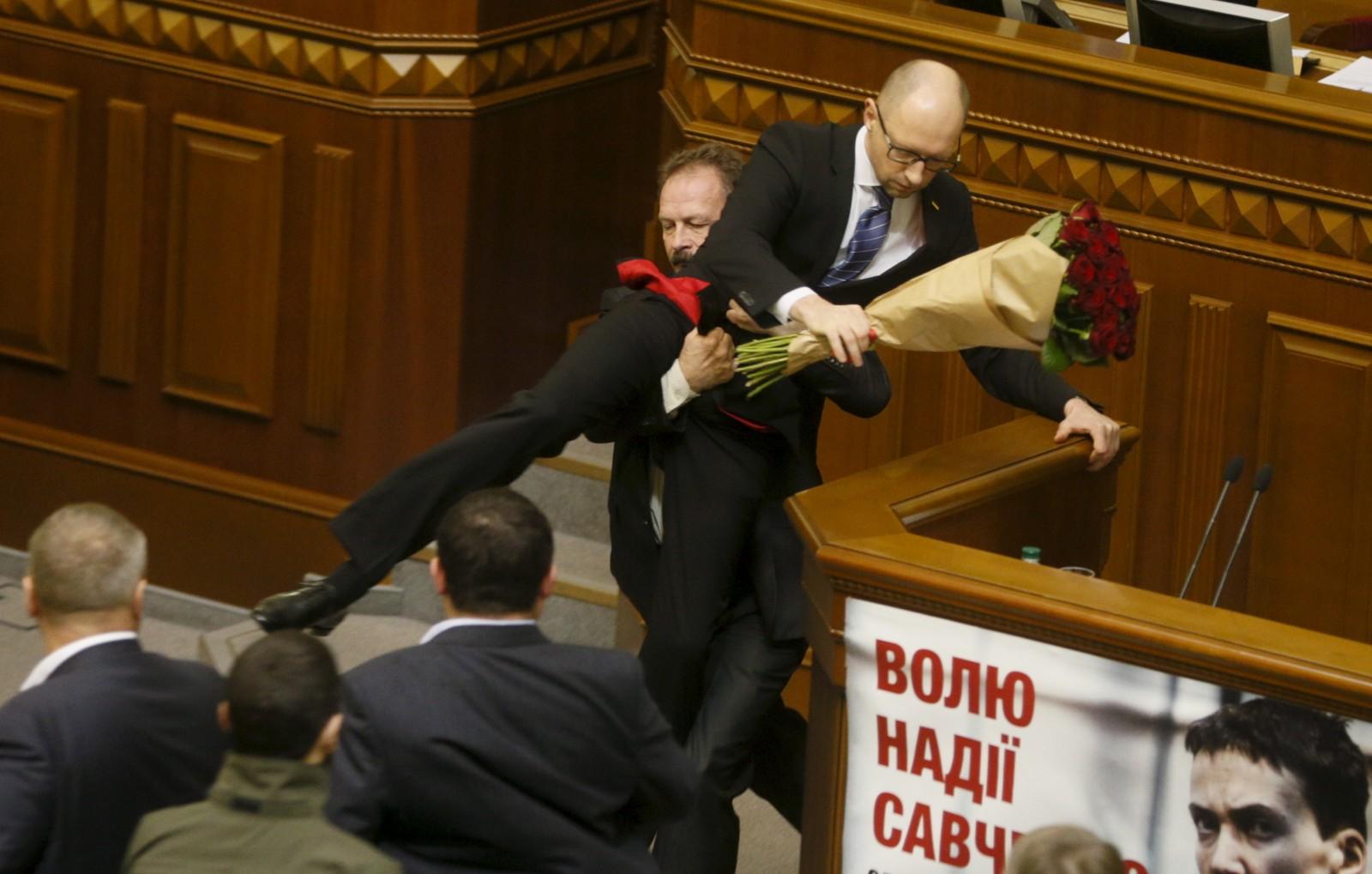 Parlamentsmedlem Oleg Barna ble så sint at han først, sarkastisk ga statsminister Arseny Yatseniuk en bukett roser, før han fysisk løftet ham ned fra talerstolen under et møte i det ukrainske parlamentet i Kiev fredag. Hendelsen førte til flere minutters bråk og slåssing, ifølge nyhetsbyrået Reuters.