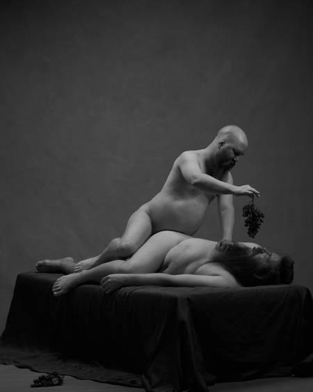 To nakne menn med skjegg ligger på en svart seng. Han ene er kraftig og han andre er skallet. Han ene mater den andre med en drueklase.