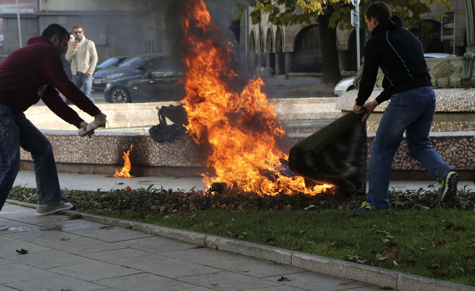 People try to save a woman who set her self on fire in front of the Presidency building in Sofia on November 3, 2014. A woman set herself on fire outside Bulgaria's presidential headquarters in Sofia on Monday, in a repeat of a series of self-immolations driven by poverty in the crisis-hit Balkan country last year, the interior ministry said. Live television footage showed firefighters carrying a burned woman on a stretcher and loading her into an ambulance.The victim, a 38-year-old woman according to the ministry, was badly burned but alive, the hospital said.