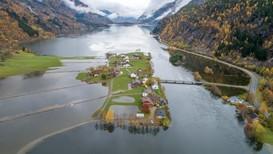 DEKKA AV VATN: Slik såg Sandvinsvatnet i Odda ut etter flaumen i helga. Markene til venstre blei dekka av vatn, og fleire hus var nære ved å få vassinntrenging.