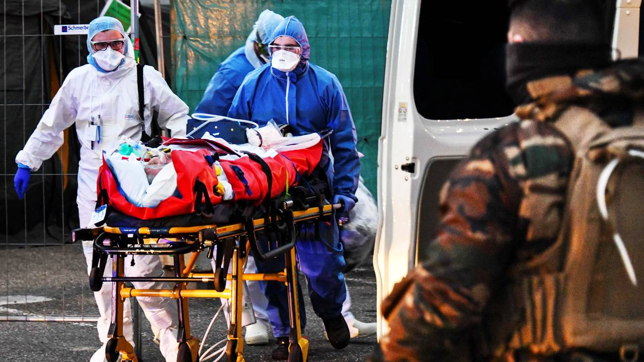 Helsepersonell bærer en koronasyk pasient til et tog som skal frakte ham til et annet område i Frankrike med ledig kapasitet på sykehusene.
