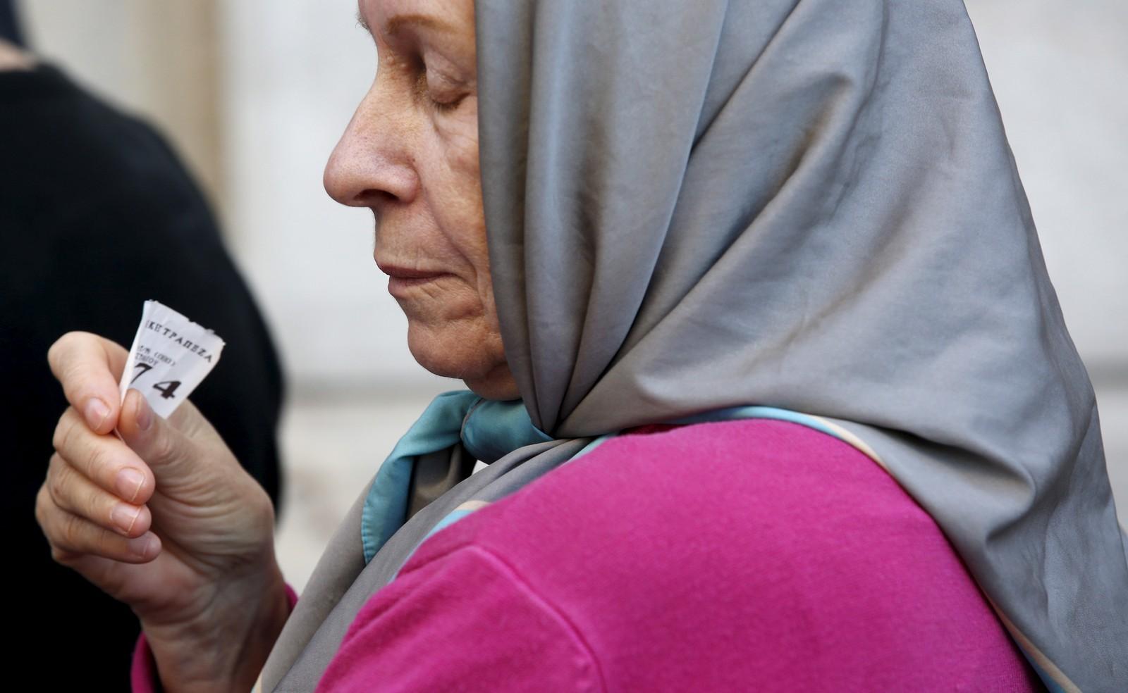 En eldre kvinne holder en kølapp i hånda mens hun venter på å få komme inn i en bank i Aten og ta ut deler av pensjonen sin.