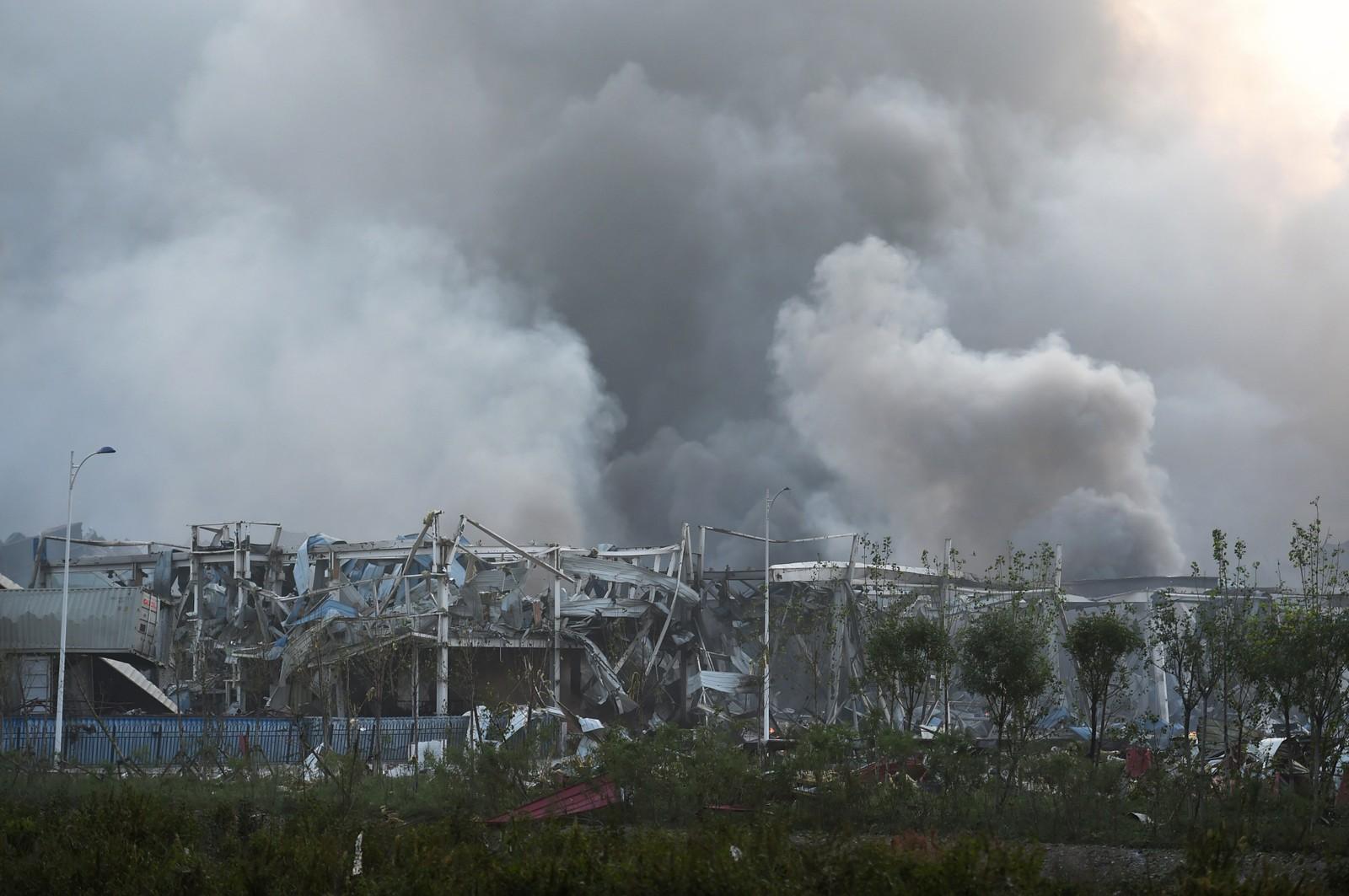 FORTSATT MYE RØYK: Røyken velter fortsatt ut fra eksplosjonsområdet når det gryr mot dag i Tianjin-provinsen.