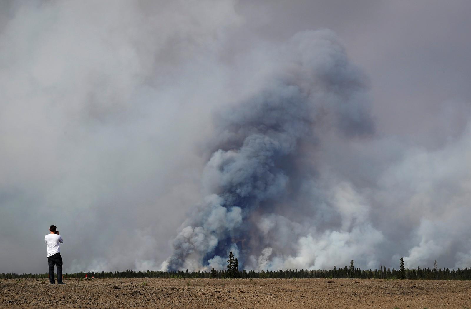 En mann tar bilde av røyken fra skogbrannen som raser nær Fort McMurray i Alberta, Canada fredag 6. mai.
