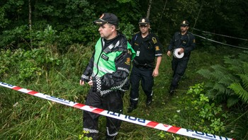 Politiet sperrer av et område i skogholtet