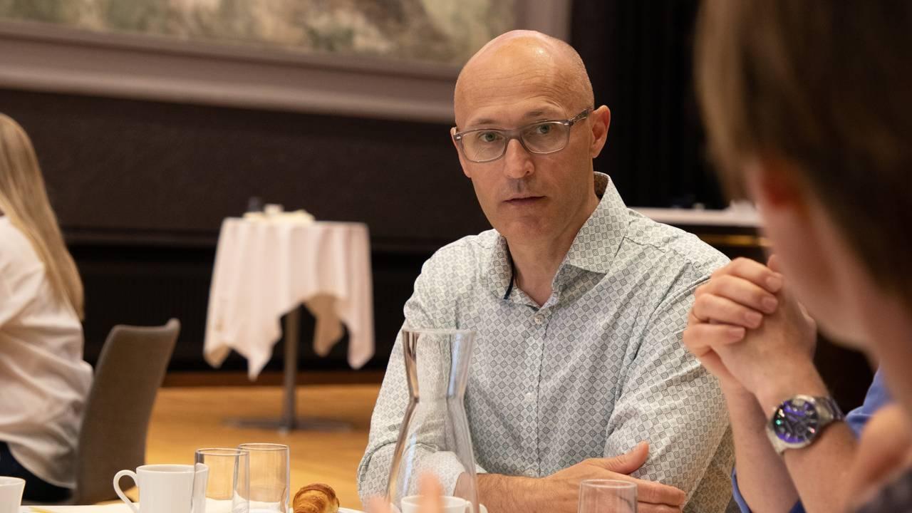 Svein Egil Dagsland sitter ved et bord i en sal på Grand Hotel. Han snakker med de andre deltaker, men man ser bare de gestikulerende hendene deres komme inn i bildet. På bordet ligger det croissanter, fargetusjer, legoklosser og notater.