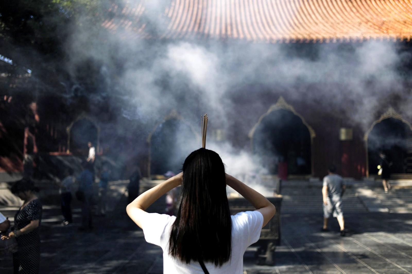 En kvinne holder røkelse mens hun ber ved Yonghetempelet i Beijing i Kina den 19. august. Det regnes som et av de største lamatemplene utenfor Tibet.
