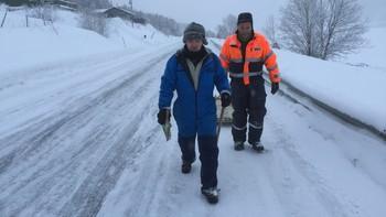 Villy Ballovarre og Torbjørn Nilsen med fiskeutstyr i hånda langs veien en vinterdag