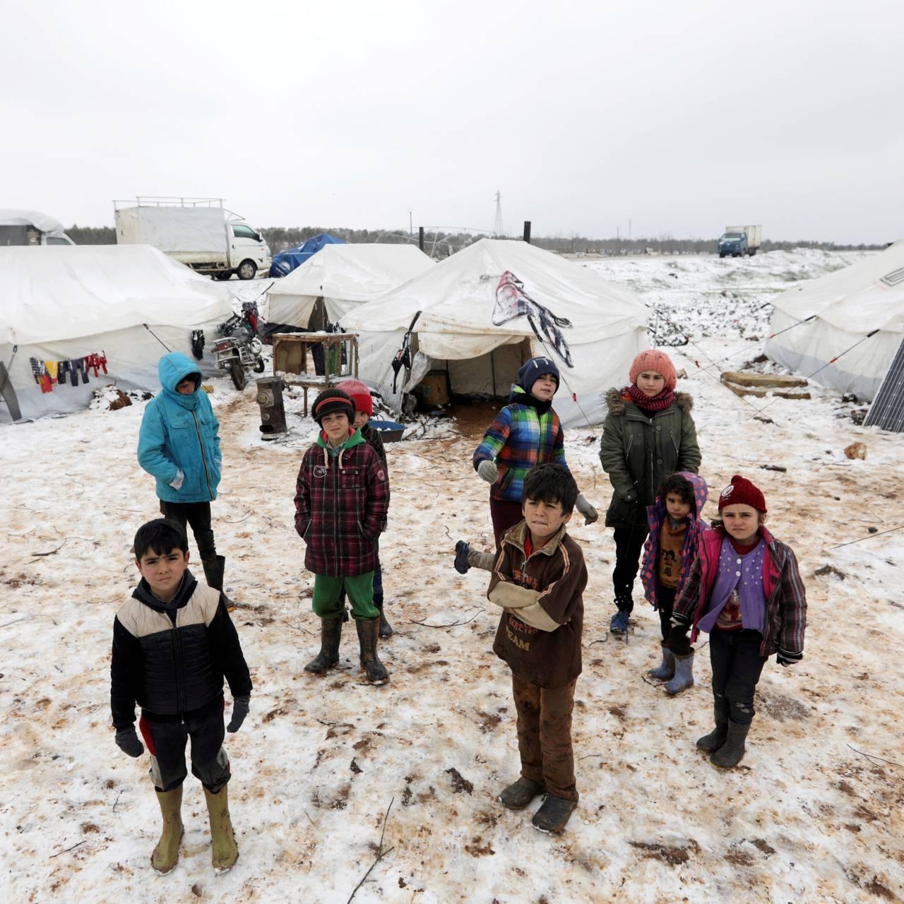 Syriske barn og voksne står i snøen ved telt i en flyktningleir i Azaz i Syria.
