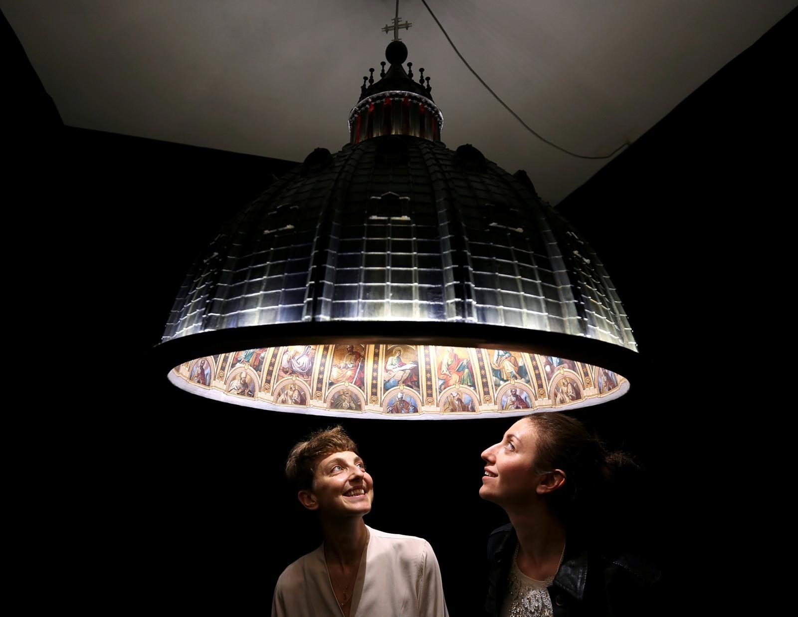 LAMPEKUPPEL: Designerne Eleonora Barbareschi (t.v.) og Alessandra Mantovani under lampen «Cupola, e luce fu», som betyr «Kuppel, og det ble lys». Den store taklampen er utformet som kuppelen på Peterskirken, både innvendig og utvendig. Lampen er laget av det italienske designbyrået Studio AMeBE og vises denne uken fram under 2016 Milano Design Week.