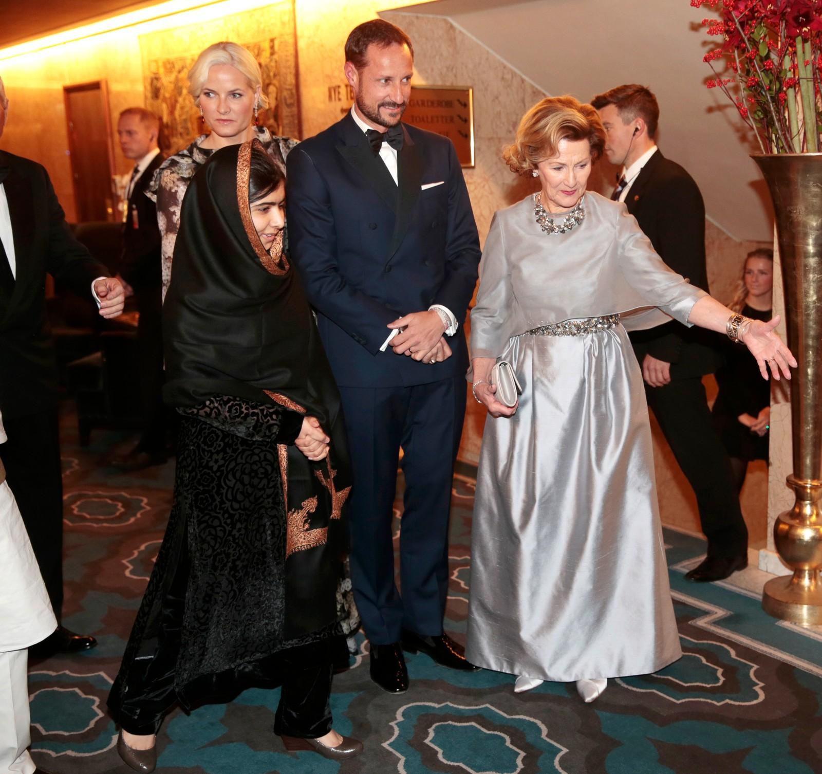 VISER VEI: Dronning Sonja og kronprinsparet på vei inn til banketten sammen med Malala.