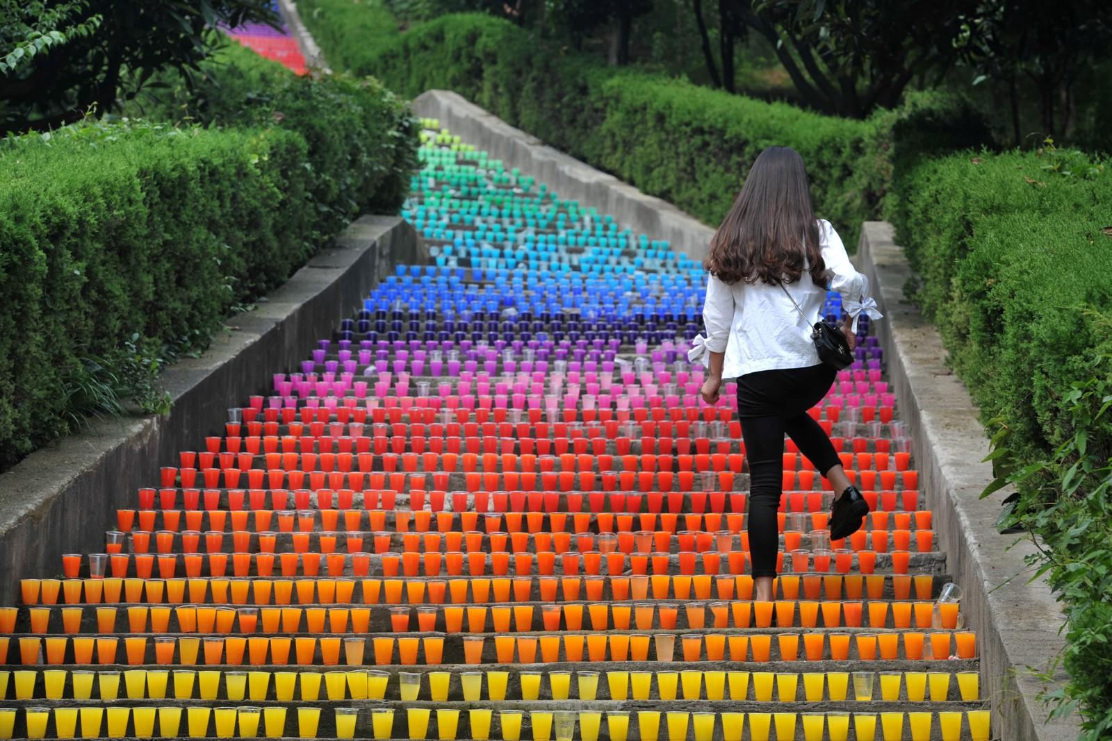 Over 5000 plastkopper i regnbuens farger ble plassert i denne trappa i Wuhan, Kina. Denne kvinnen forsøker å unngå å ødelegge kunstverket laget av fire studenter.