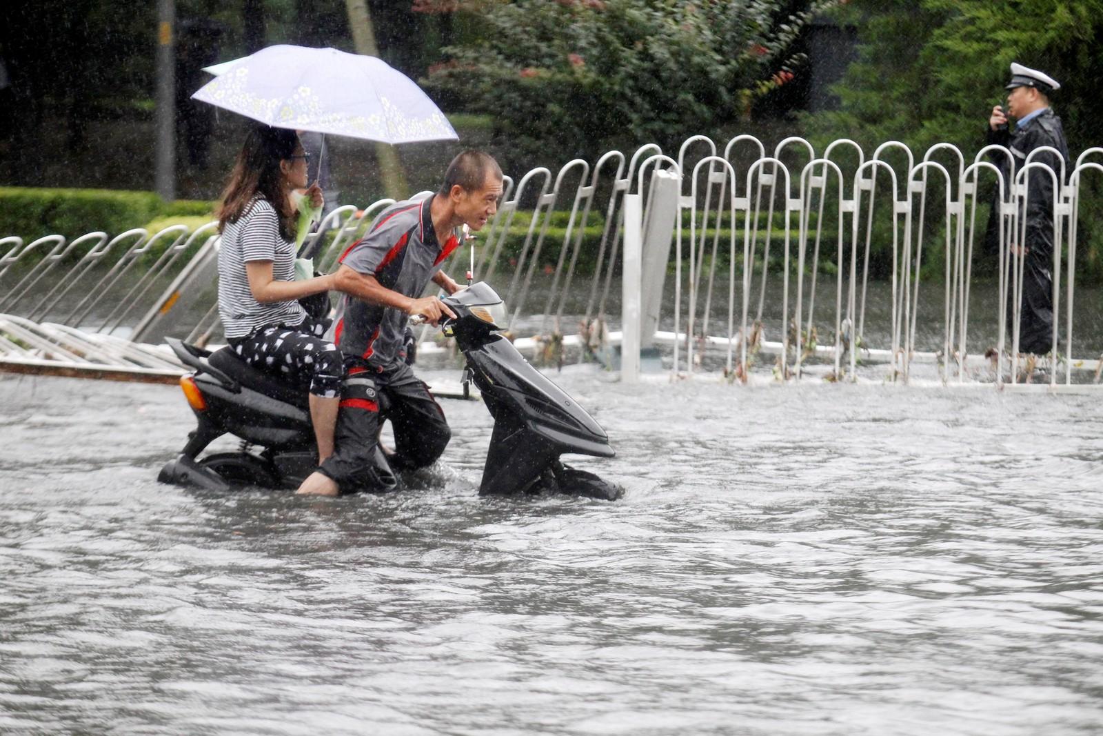 Folk kjemper seg gjennom store vannmasser i hovedstaden Beijing