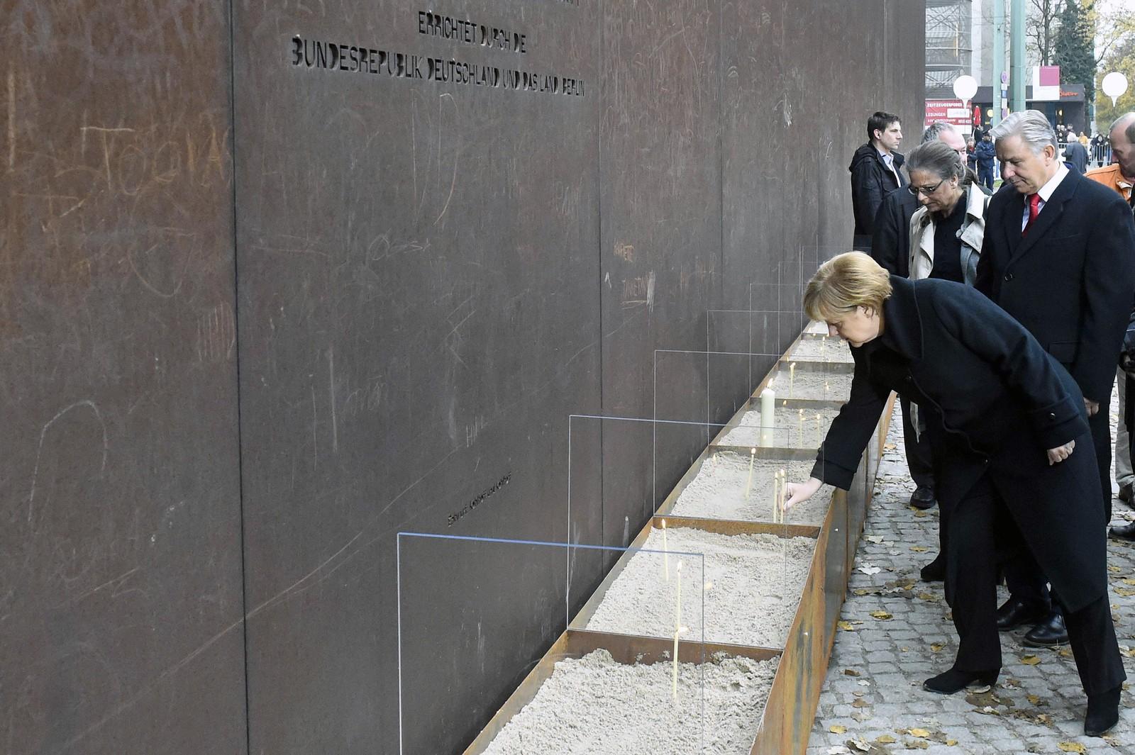 Angela Merkel og ordfører Klaus Wowereit tenner lys ved minnesmerket for de falne ved Berlinmuren.