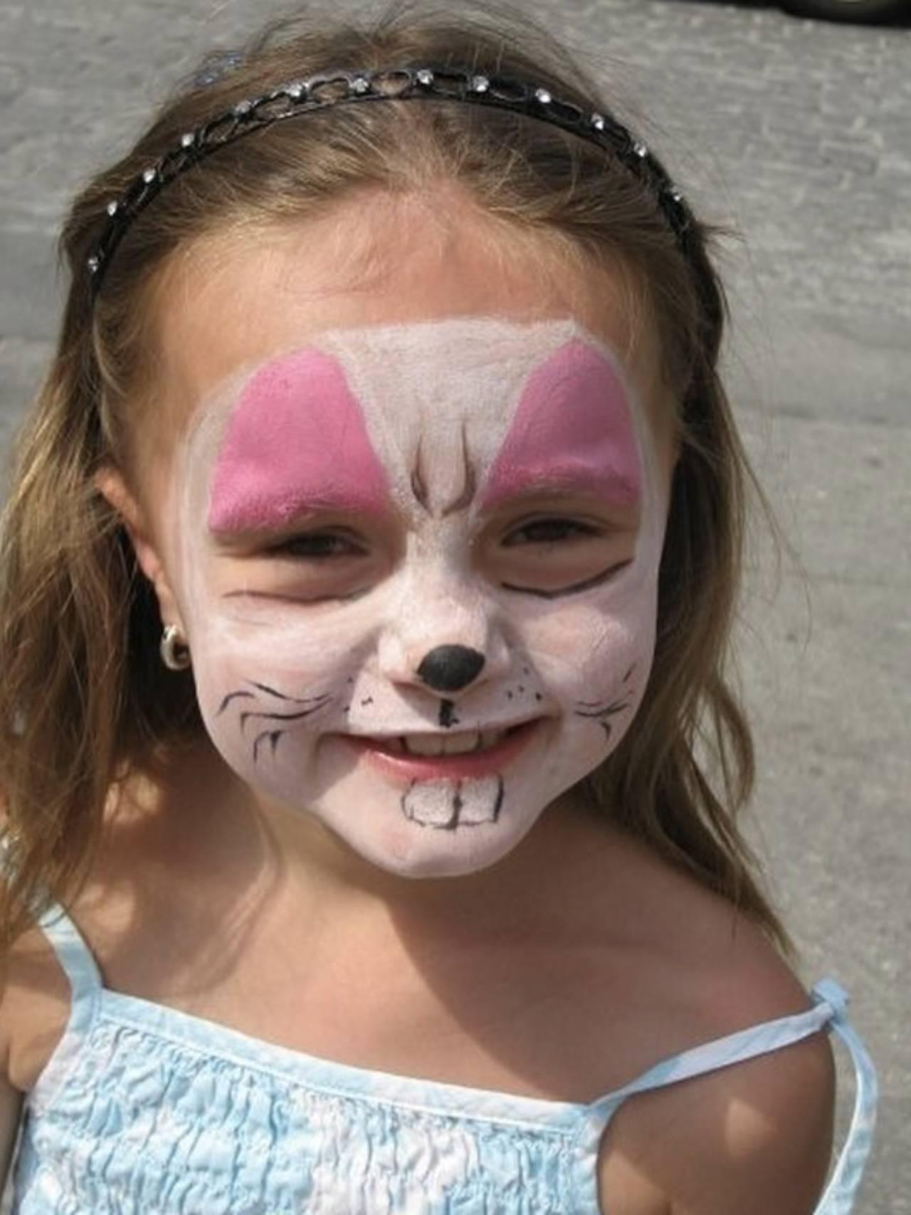 Andrine som barn. Smiler og har på seg rosa, hvit og svart ansiktsmaling
