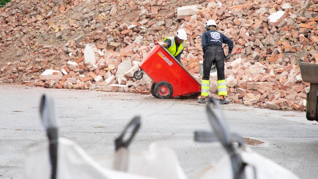 En gigantisk haug med røde teglstein ligger på anleggsplassen. I bakgrunnen skimtes en gravemaskinen og en bolig. I forgrunnen ser man avfallssekker. Ved enden av murhaugen står det to sommervikarer og tømmer en tralle med avfall.