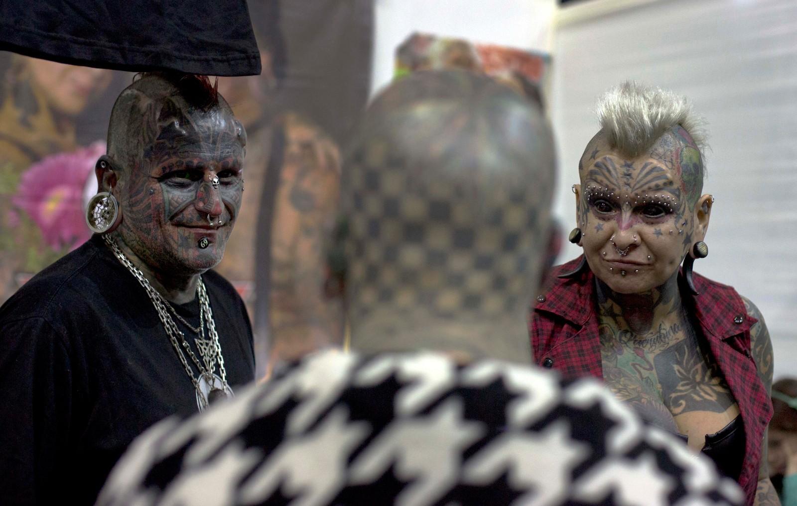Victor Peralta og hans kone Gabriela Peralta, diskuterer det vi bare kan anta er tatoveringer med Matt Gone under en tatoveringsfestival i Lima, Peru. Peralta holder verdensrekorden for ektepar med flest kroppsutsmykninger.