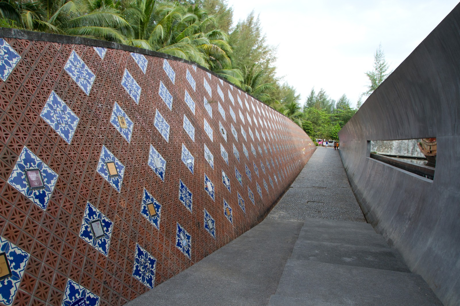 Hele minneveggen i Nam Khem memorialpark. Langs veggen er det plassert flere minneplaketter hvor navn til omkomne er skrevet inn. Ikke alle pårørende ønsket navnet til sine her.