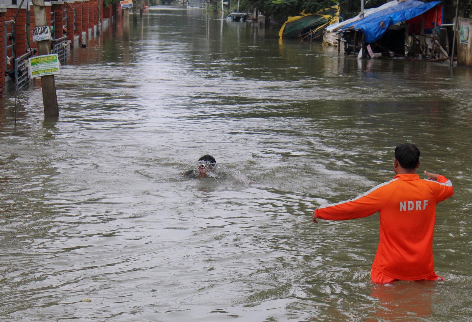 En mann som jobber for den nasjonale krisestaben er på vei for å redde en gutt som har falt i vannet i Chennai. Dette er det kraftigste regnfallet på hundre år i delstaten Tamil Nadu i India.