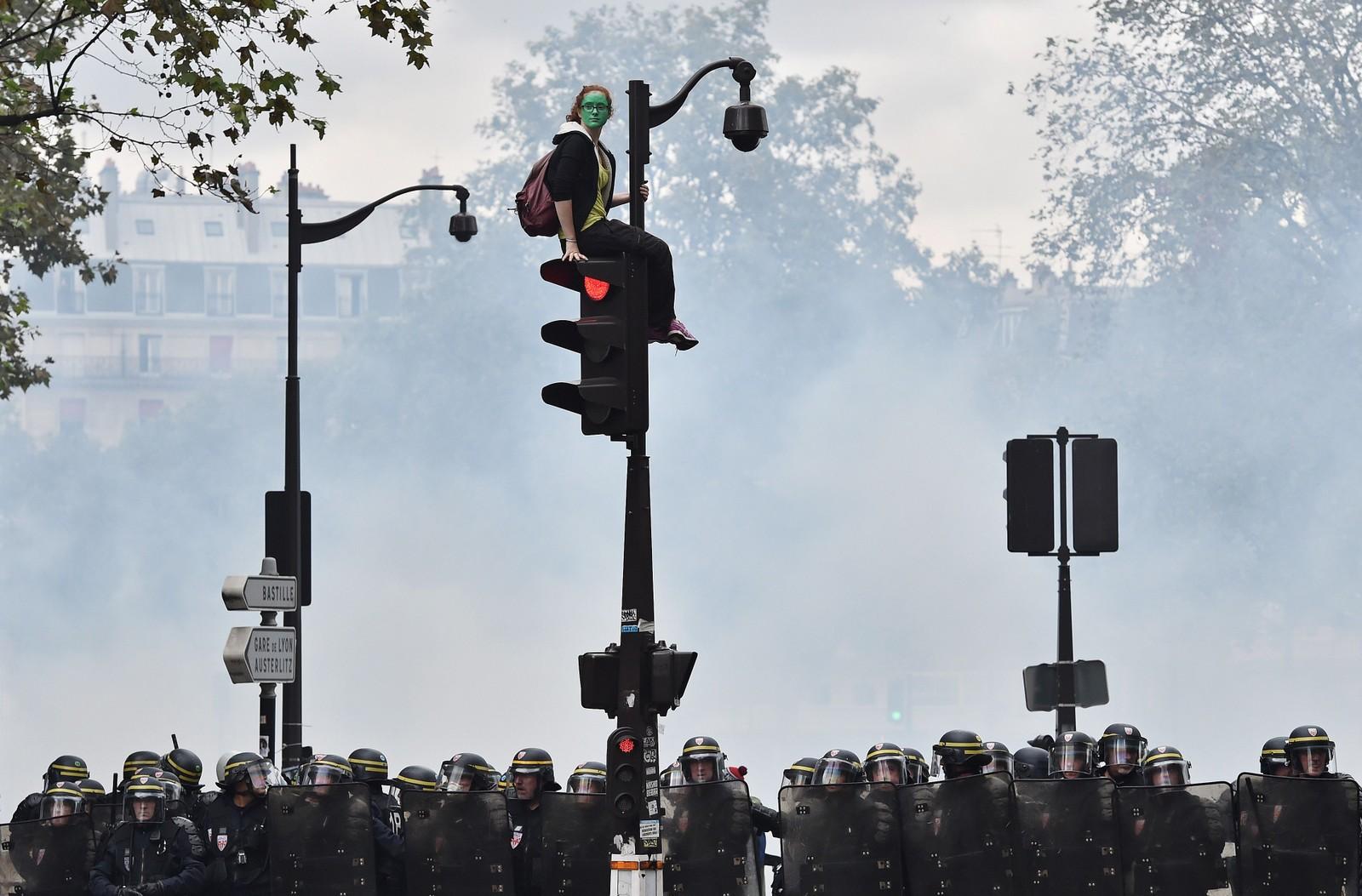En demonstrant med grønnmalt ansikt har klatret opp i et trafikklys mens fransk opprørspoliti står på bakken under i forbindelse med en demonstrasjon mot myndighetenes svært omstridte arbeidsreform i Paris 15. september. Politiet brukte tåregass og sjokkgranater mot de rundt 13.000 demonstrantene, som på sin side kastet brannbomber mot politiet.