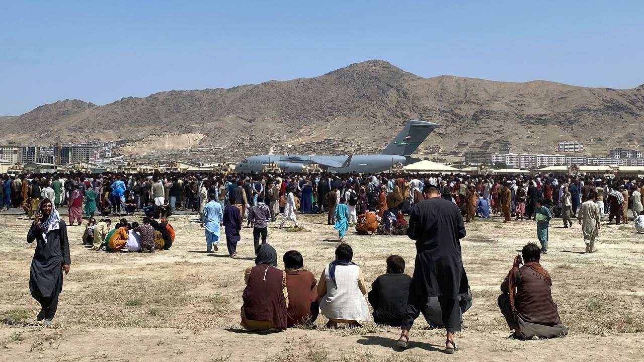 Menneskemengder inne ved rullebanen på flyplassen i Kabul foran et militært transportfly mandag 16. august 2021