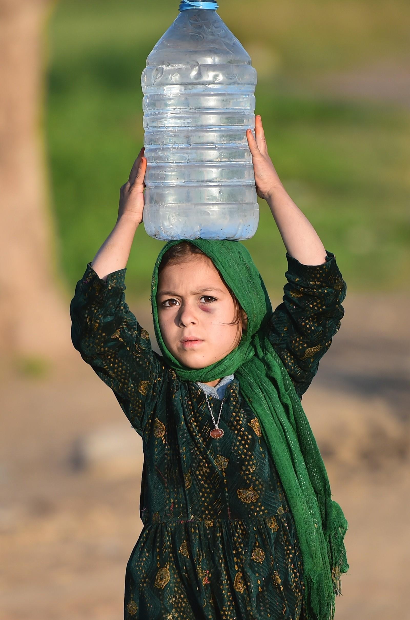 En pakistansk jente bærer vann i Islamabad, Pakistan.