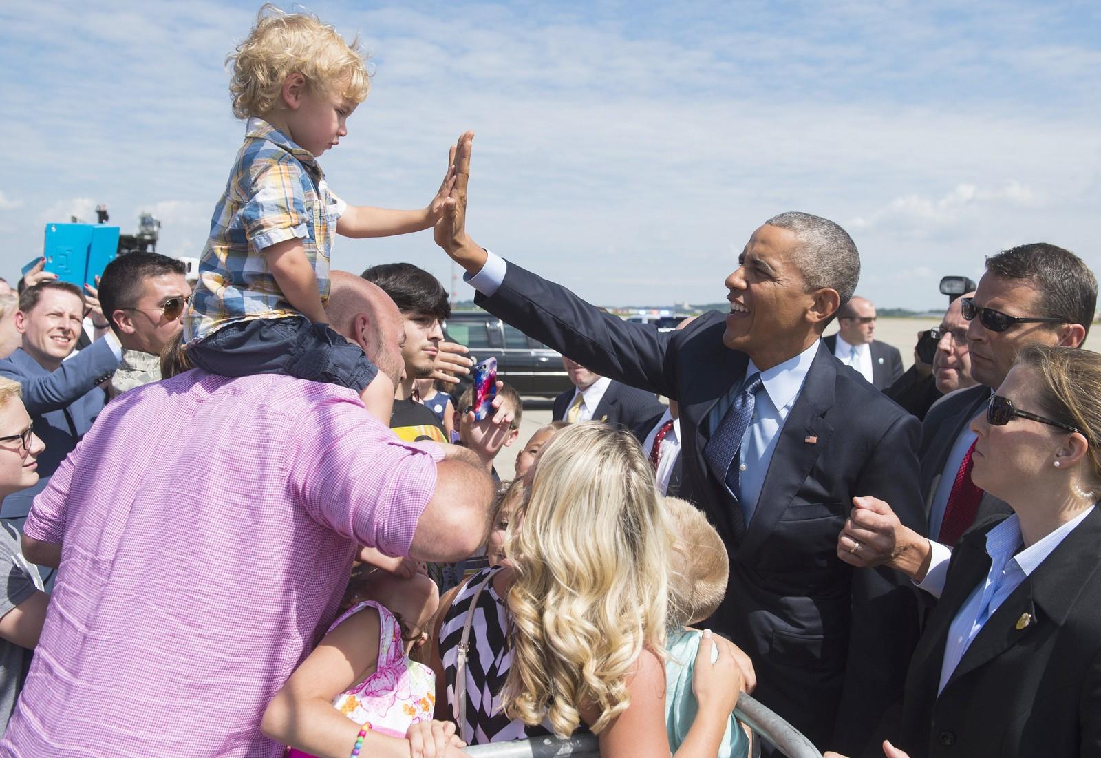 """Elliot Riley (2) tar en """"high five"""" med USAs president Barack Obama på flyplassen i Pittsburgh, Pennsylvania.  Obama ankom byen 21. juli for å holde tale under en veterankonferanse, før han hastet videre for å gjeste """"The Daily Show"""" med Jon Stewart."""