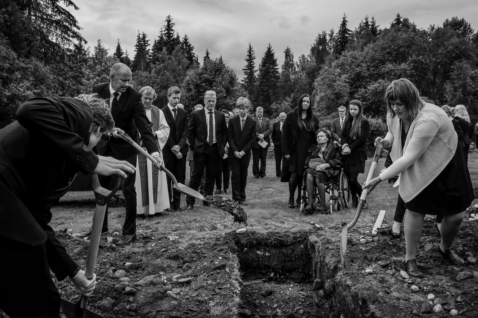 1. pris dagligliv i Norge: 16. juli kl. 14.15 ble min far gravlagt i Øyer i Gudbrandsdalen. Min far var mørkredd. Derfor hoiet han alltid før han rundet hushjørnet hjemme. Hvis det var noen på den andre siden som ville skremme han, skremte han dem like gjerne først. Og det slo meg i dag, da vi hadde sunget høyt og grått stille. Da vi senket han ned og la jord over kisten. Han hadde rundet hjørnet for aller siste gang. Jeg tror ingen hørte det, men jeg hoiet litt, jeg. Presten i Øyer har innført en gammel tradisjon om at bygdefolket skal gravlegge bygdas beboere. Etter at vi nærmeste pårørende hadde tatt de første spadetakene, ble vi avløst av venner, naboer og bekjente av min far. Sammen dekket vi til graven. Det hele var rart der og da, men jeg tror bygdefolket som stod min far nær, fikk tatt farvel på en fin måte. Juryens begrunnelse: En personlig og uventet historie. Vi har aldri sett at familien til avdøde selv tar spadetakene i en begravelse. Det gjør at vi stopper opp og dveler ved dette bildet.
