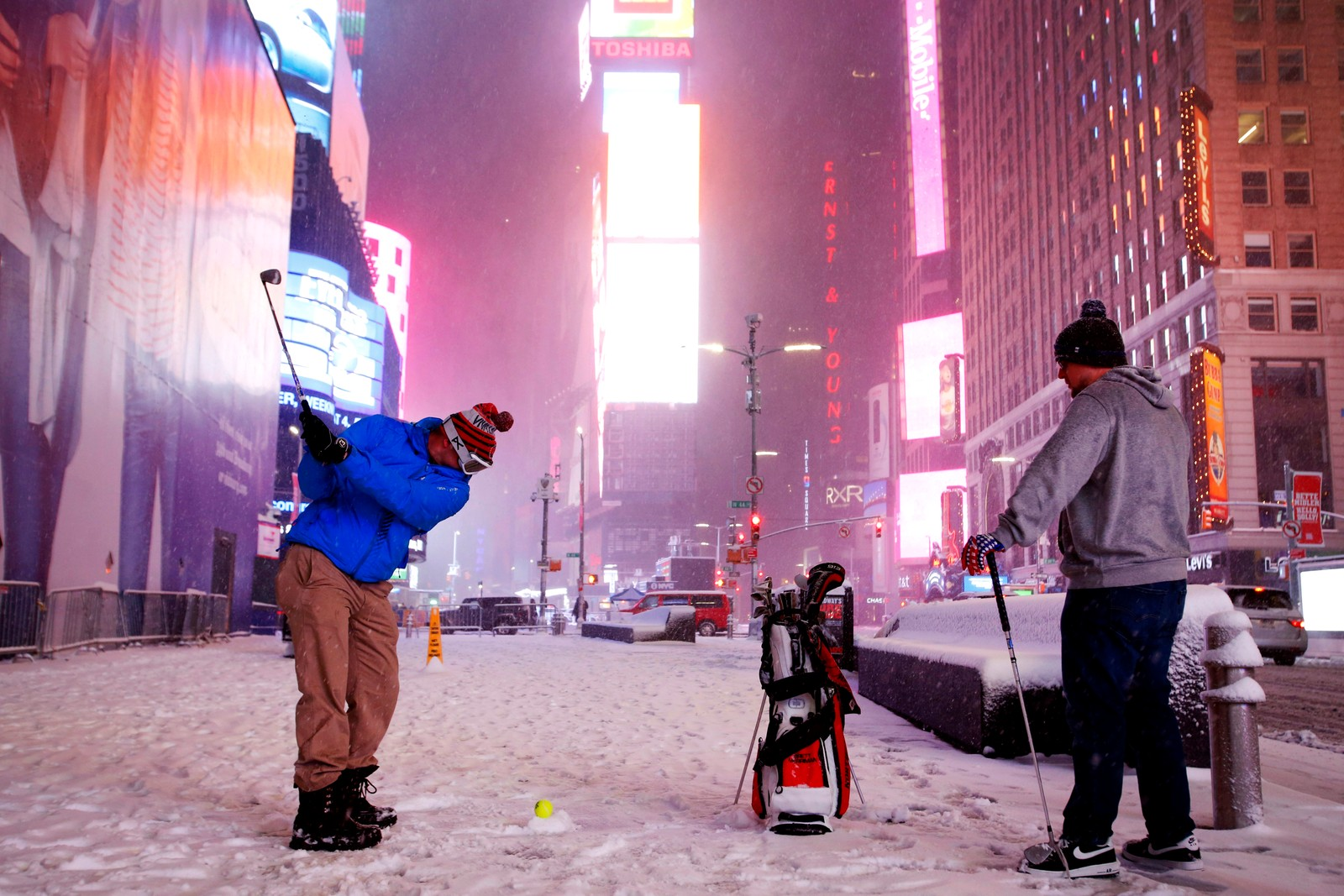 Det finnes ikke dårlig vær... To menn spiller golf under snøværet på Times Square i New York.