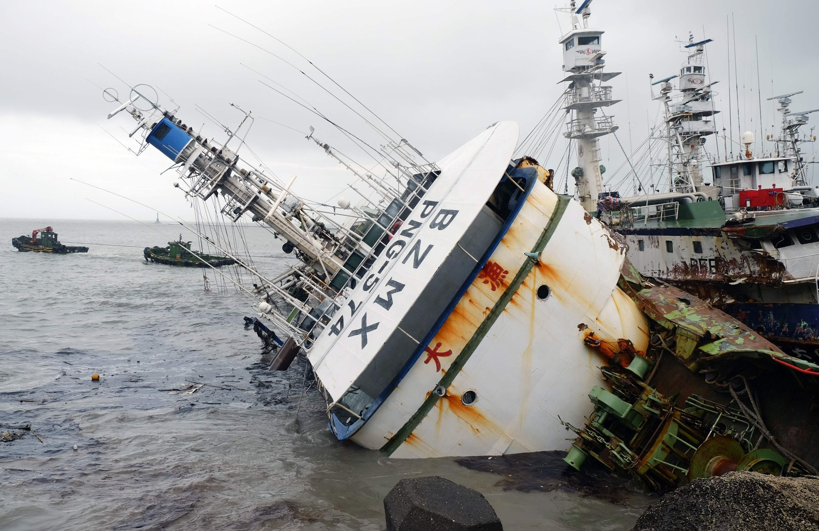 MYE VIND: To båter forsøker å redde en fiskebåt som veltet under stormen i Taiwan.