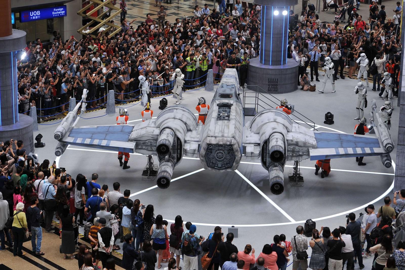 Store og små Star Wars-fans bivåner et X-Wing-fartøy i faktisk størrelse under et arrangement på Changi-flyplassen i Singapore.