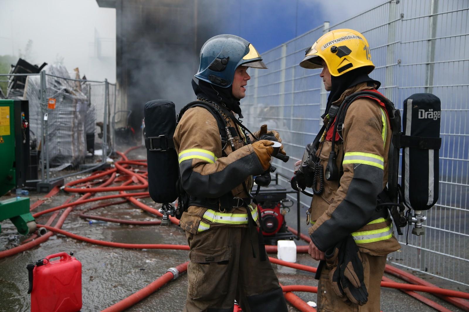 To brannfolk tar seg en kaffe. I over 16 timer har de arbeidet med å slukke flammene som startet hos Jysk på Hunstadsenteret.